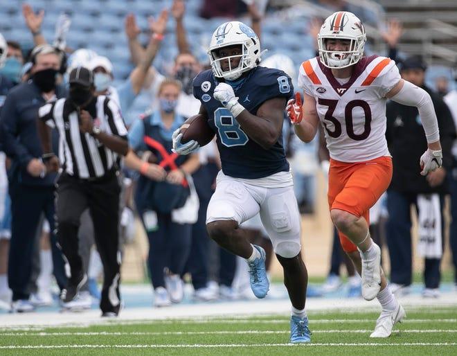 Michael Carter de Carolina del Norte (8) se separa de Tyler Matheny de Virginia Tech para un touchdown de 62 yardas en el último cuarto en el Kenan Stadium en Chapel Hill, NC