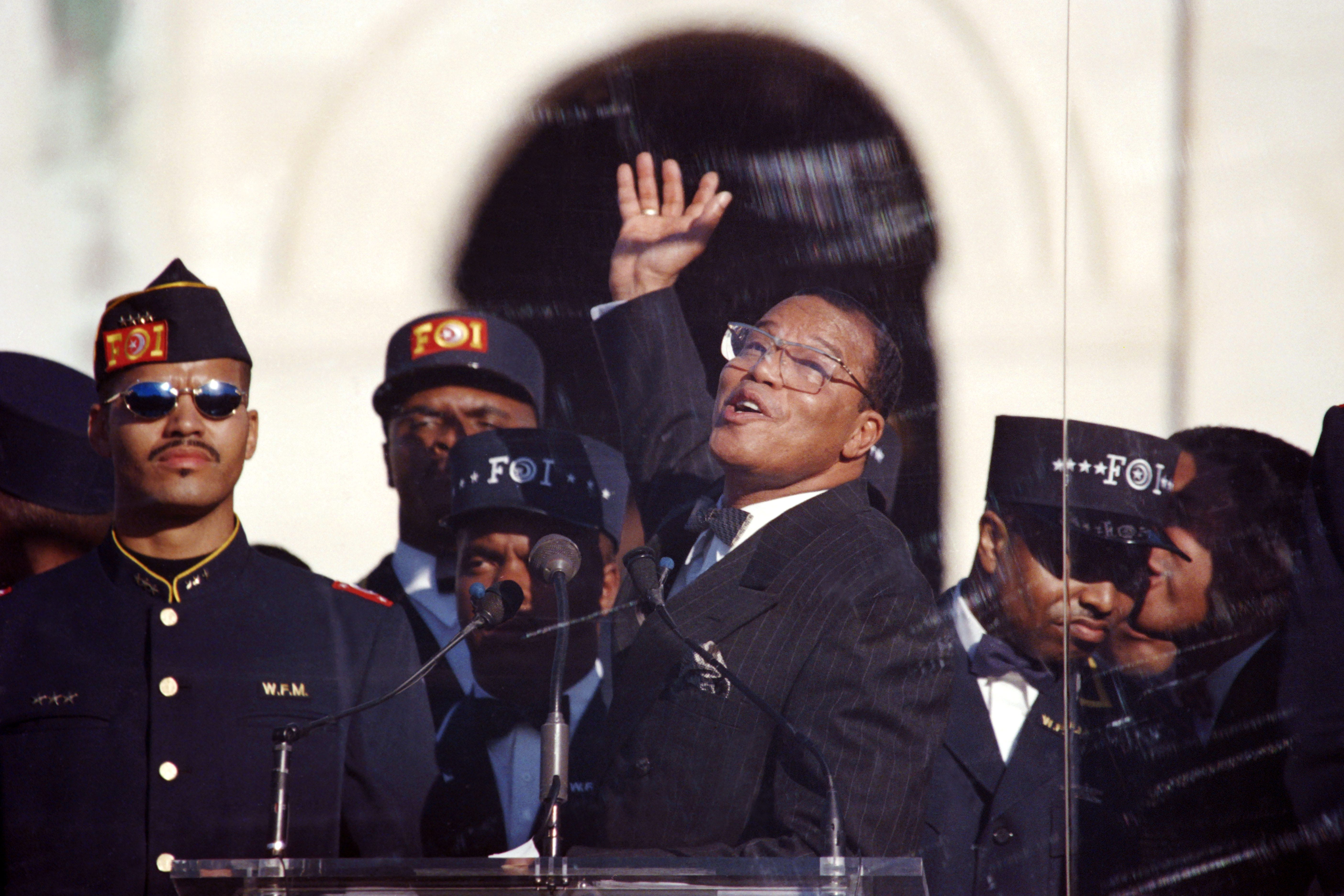 Nation of Islam leader Louis Farrakhan raises his hand behind bulletproof glass as he speaks in front of the Capitol Building at the Million Man March on Oct. 16, 1995.
