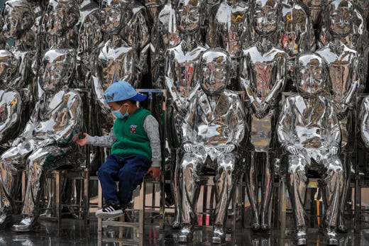 A child wearing a face mask to help curb the spread of the coronavirus tries to hold a statue's hand as he sits in an art installation on display at a shopping mall in Beijing, Sunday, Oct. 11, 2020. Even though the spread of COVID-19 has been all but eradicated in China, the pandemic is still surging across the globe with ever rising death toll.