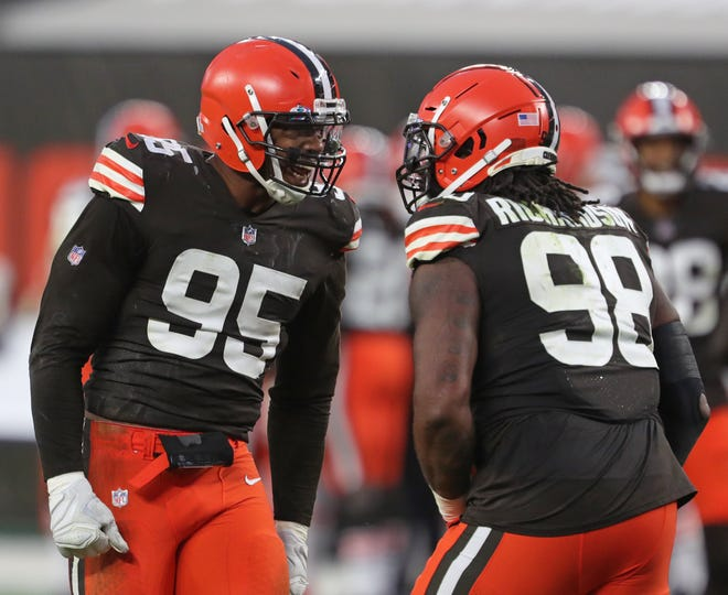 Cleveland Browns defensive end Myles Garrett (95) celebrates with Cleveland Browns defensive tackle Sheldon Richardson (98) after a intentional groundING call against Indianapolis Colts quarterback Philip Rivers (17) during the second half of an NFL football game, Sunday, Oct. 11, 2020, in Cleveland, Ohio. [Jeff Lange/Beacon Journal]