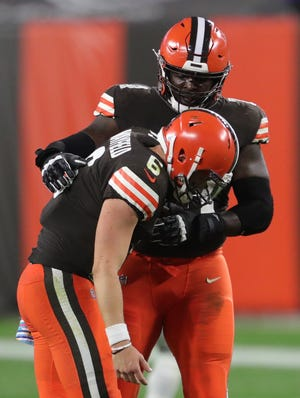Cleveland Browns quarterback Baker Mayfield (6) is helped to his feet by Cleveland Browns offensive tackle Chris Hubbard (74) after throwing an interception during the second half of an NFL football game against the Indianapolis Colts, Sunday, Oct. 11, 2020, in Cleveland, Ohio. [Jeff Lange/Beacon Journal]