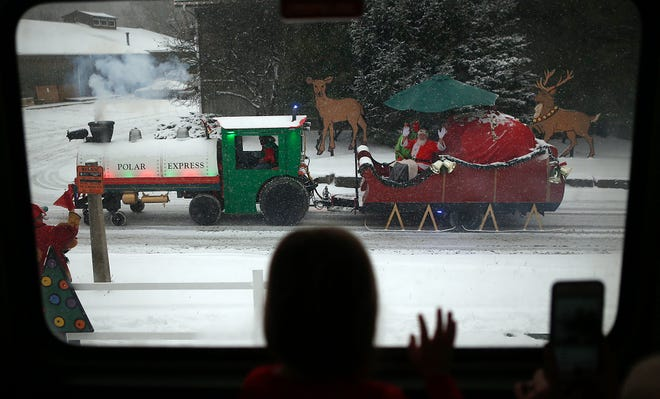 A child waves to Santa at the North Pole on from the Polar Express on Tuesday, Dec. 12, 2017, at Coventry High School in Akron, Ohio. FirstEnergy and the LeBron James Family Foundation rented the train ride out for Akron third graders in the I Promise program. (Leah Klafczynski/Beacon Journal/Ohio.com)