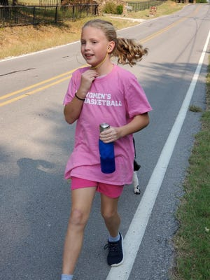 Arli Woolly running alongside the road near her house in Ardmore. Woolly is running to raise awareness for breast cancer and funds to create care packages for newly diagnosed women.