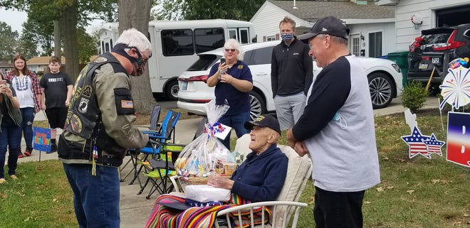 Richard Sprow (seated) of Bristol Township is congratulated by a member of the Warrior Watch organization as his son Rick Sprow (right) and other family members, friends and neighbors look on Saturday during a drive-by parade to honor Sprow, a World War II veteran who turns 94 on Tuesday.