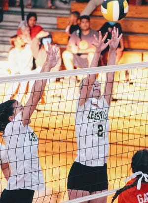 Leesville's Emily Willis (2) and Madison Joiner go up for the tandem block during the Lady Cats' district loss to Beau Chene on Tuesday at home. Willis had several blocks and contested many other kill attempts during the match.