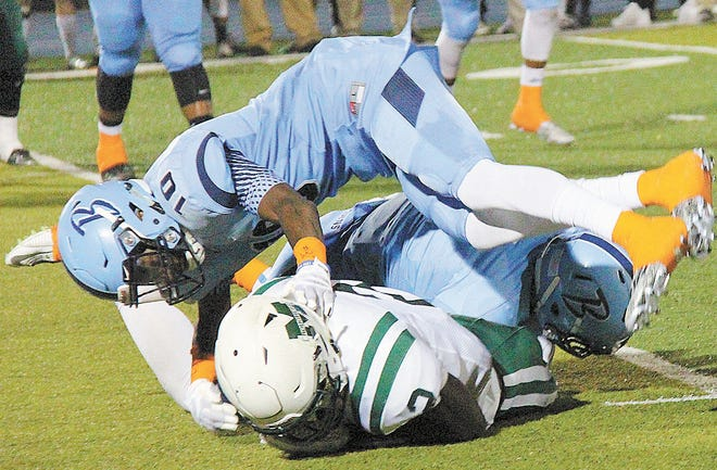 A.J. Parker, left, helps bury a Muskogee player during Bartlesville High action in 2015. Parker is now a senior star cornerback in the Big 12 for Kansas State.