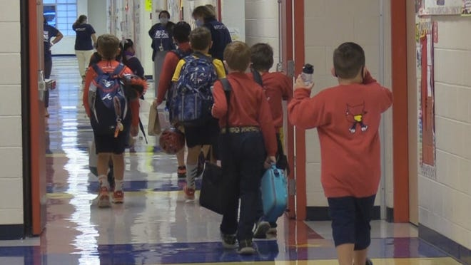 Students at Red Cedar Elementary walk to their classroom on the first day of in-person instruction. District officials said students will only walk in one direction in hallways during the pandemic.