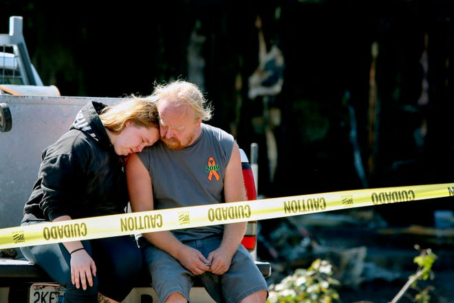 Kelsey Detter, left, embraces her father James Detter outside the scene of a fire in De Soto on Sunday. The four people killed in the eastern Missouri house fire included a married couple, their daughter and a granddaughter, the victims' family members said.