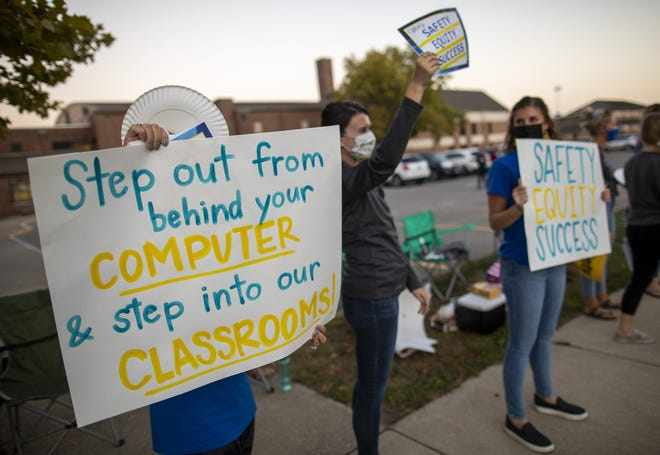 Parents and teachers in the Gahanna Jefferson Education Association rally for a new employment contract outside Gahanna Lincoln High School on Oct. 7. More than 100 people in the teachers union lined Hamilton Road with signs and held candles.