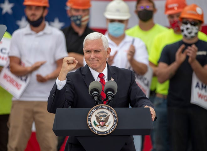 Vice President Mike Pence gives a fist pump as he speaks during a campaign rally at Nicholas Savko & Sons construction company in Columbus on Monday.