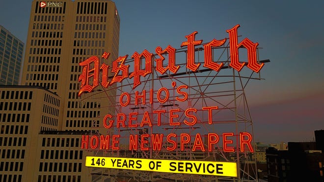 The orange neon Columbus Dispatch sign looms over downtown Columbus.    (Columbus Dispatch photo by Doral Chenoweth III)