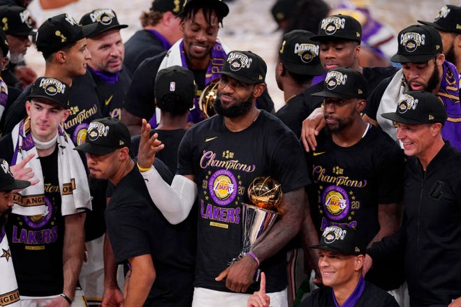 LeBron James holds the championship trophy after leading the Lakers to a title-clinching 106-93 victory over the Heat in Game 6 of the NBA Finals on Sunday night.