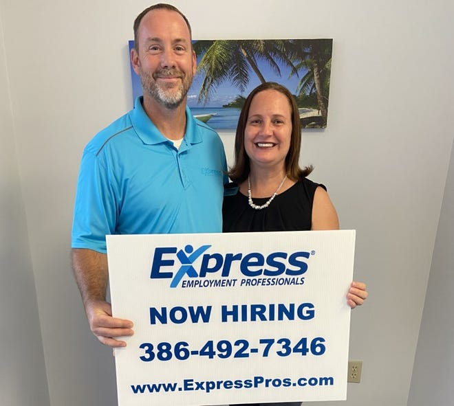 Bill and Michelle Brown, franchise owners of the Express Employment Professionals staffing agency in Daytona Beach, hold a hiring sign at their office on Beville Road. The couple are the organizers of a Drive-Through Job Fair and Food Outreach event that will be held Saturday, Oct. 17, 2020, from 9 a.m. to noon at the Pictona pickleball complex at 1060 Ridgewood Ave. in Holly Hill. Nearly a dozen area employers have signed up to participate. Food bags will be given out by volunteers with Calvary Christian Church's Daytona Dream Center food outreach program.