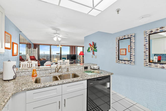 The kitchen, featuring new granite countertops, a new refrigerator, white cabinets and a bar-height eating counter, overlooks an open setting, with views of the balcony and ocean.