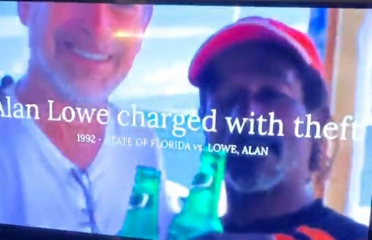 This still frame shows a Milissa Holland campaign ad showing Alan Lowe with a Black man while accusing Lowe of being charged with theft.
