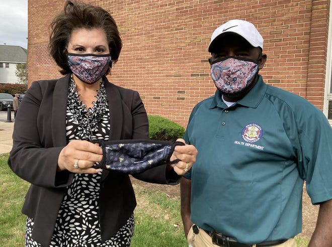 Nina Ferraro, Highmark Health's manager of community affairs, and Zakaria Sharif, a public health educator with the Erie County Department of Health, display one of the 2,000 face masks Highmark donated Monday to the health department for distribution to county residents.