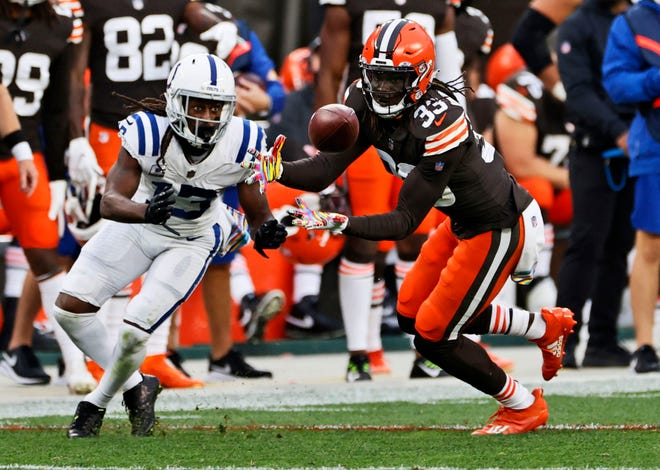 Cleveland Browns defensive back Ronnie Harrison, right, intercepts the ball ahead of Indianapolis Colts wide receiver T.Y. Hilton, left, during the second half of an NFL football game, Sunday, Oct. 11, 2020, in Cleveland. Harrison returned the ball for a 47-yard touchdown on the play.