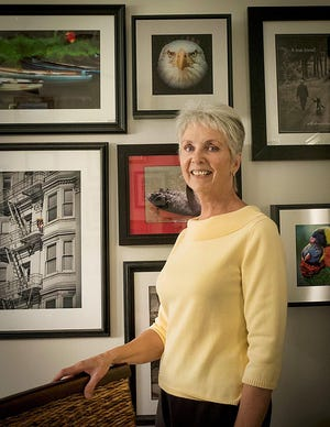 Rebecca Samler, marketing co-chair for the Photographic Arts Society of Northwestern Pennsylvania, stands in front of her collection of artwork. Pieces by Samler will be among those in the society's virtual show.