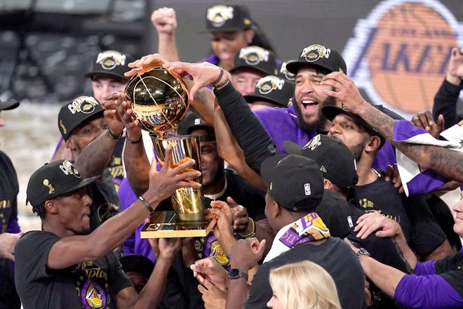 Los Angeles Lakers players celebrate after defeating the Miami Heat 103-88 in Game 6 of the NBA Finals Sunday in Lake Buena Vista, Florida. [MARK J. TERRILL / AP]