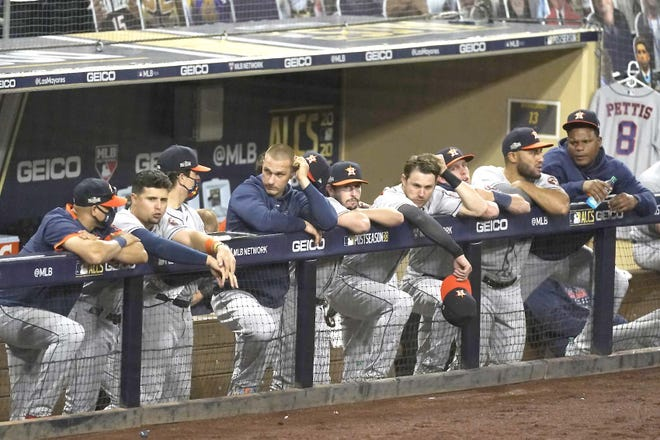 The Houston Astros watch from their dugout Sunday during the seventh inning of Game 1 of the American League Championship Series against the Tampa Bay Rays in San Diego. [ASHLEY LANDIS / AP]