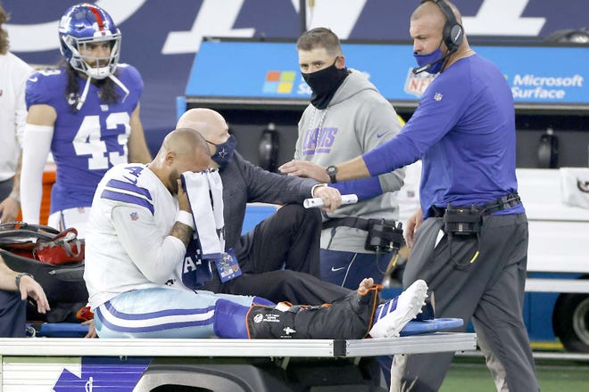 An emotional Dallas Cowboys quarterback Dak Prescott wipes his face with a towel as he is carted off the field after suffering a leg injury during the second half of Sunday's game against the New York Giants in Arlington, Texas. The Giants' Nate Ebner (43) and staff look on. [RON JENKINS / AP]