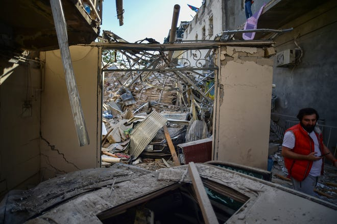 A man walks near damaged buildings a day after shelling by Armenian's artillery during fighting over the separatist region of Nagorno-Karabakh, in Ganja, Azerbaijan, on Monday. Armenia and Azerbaijan on Monday have accused each other of attacks over the separatist territory of Nagorno-Karabakh despite a cease-fire deal brokered by Russia in an effort to end the worst outbreak of hostilities in decades.