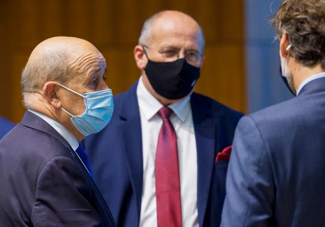 French Foreign Minister Jean-Yves Le Drian, left, and Poland's Foreign Minister Zbiegniew Rau, center, attend a meeting of European Union foreign ministers at the European Council building in Luxembourg on Monday. European Union foreign ministers approved impose sanctions on Russian officials and organizations blamed for the poisoning of opposition leader Alexei Navalny with a Soviet-era nerve agent.