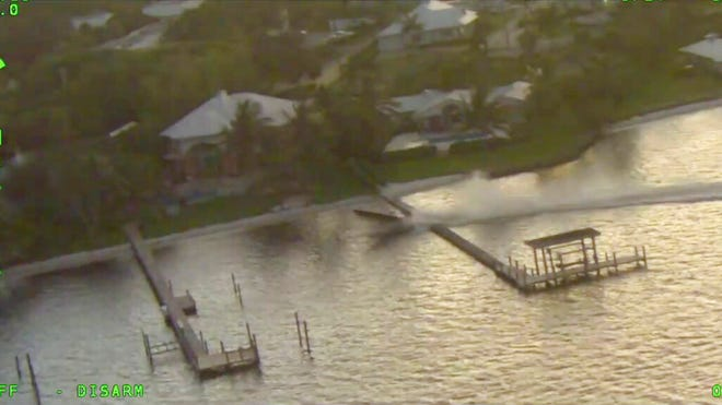 This Oct. 10, 2020, photo provided by the Martin County Sheriff's Office shows an unmanned boat going over a dock on the St. Lucie River in Florida. Three people conducting a photo shoot on the boat somehow fell overboard, leaving the 24-foot vessel unmanned and out of control. The boat circled the men numerous times, forcing them to dive underwater so it wouldn't run them over. The boat then straightened out, hit a concrete dock, went airborne and hit a second dock before coming to a stop.