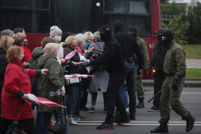 "People, most of them elderly women, argue with plainclothes police officers during an opposition rally to protest the official presidential election results in Minsk, Belarus, on Monday. Riot police clashed with protesting pensioners in central Minsk on Monday. The pensioners marched in a column through central Minsk, carrying flowers and posters with slogans such as ""The grandmas are with you (protesters)."""