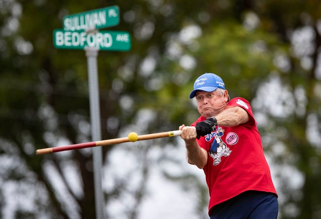 Brooklyn Bums Sid Tweady connects with the rubber ball during a Wycliffe Stiffs stickball league playoff game in Wellington, Tuesday, March 10, 2020. The street sign in background marks the intersection of the former site of Ebetts Field in Brooklyn. The stickball league recently canceled its 19th season because of concerns about the novel coronavirus pandemic.