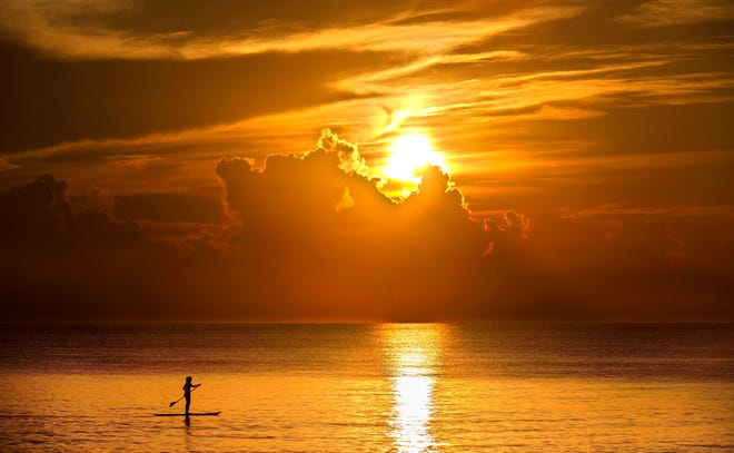 A woman paddleboards off Midtown Beach in Palm Beach at sunrise Monday.