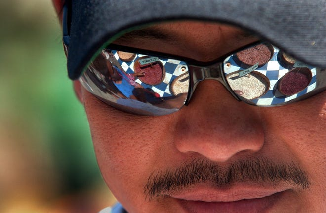 A display of various beans is reflected in the glasses of Robert Taya of Tracy at the 17th annual California Dry Bean Festival Aug. 3, 2003, in downtown Tracy.