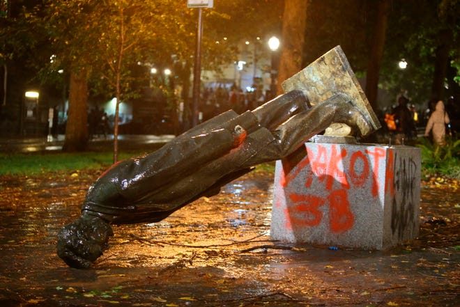 A group of protesters toppled statues of former presidents Theodore Roosevelt and Abraham Lincoln in Portland's South Park Block late Sunday, Oct. 11.