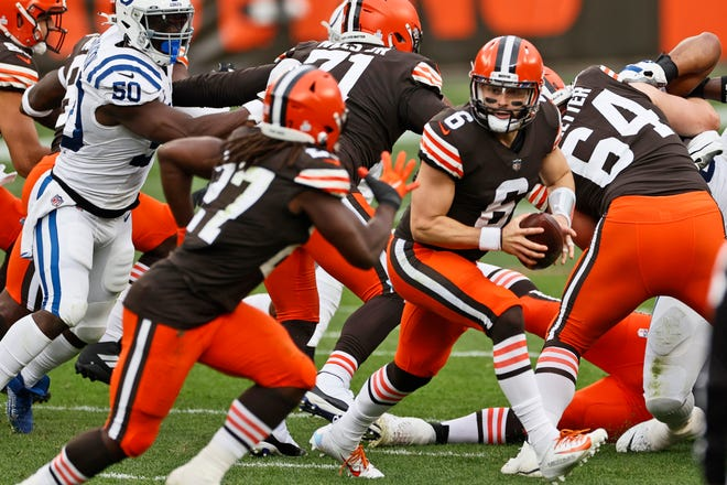 Browns left tackle Jedrick Wills Jr. (71, top middle) blocks as quarterback Baker Mayfield looks to hand off to Kareem Hunt during the first half of a game against the Colts, Sunday, Oct. 11, 2020, in Cleveland. (AP Photo/Ron Schwane)