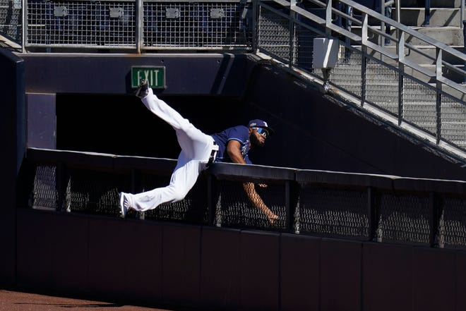 Tampa Bay Rays right fielder Manuel Margot falls over a right field wall after catching a foul ball by Houston Astros center fielder George Springer during the second inning in Game 2 of a baseball American League Championship Series, Monday, Oct. 12, 2020, in San Diego.(AP Photo/Gregory Bull)
