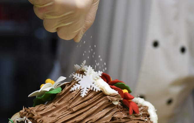 Hans Westermark. lead decorator, at Apple Annie's Bake Shop, decorates a buche de noel at the shop in Wilmington, N.C., Monday, October 12, 2020. The long-time Wilmington bakery celebrated it's 35th anniversary in September.    [MATT BORN/STARNEWS]