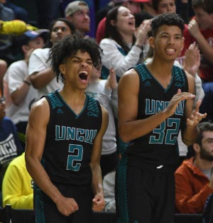 Shykeim Phillips (left), John Bowen and UNCW hope to find a few more celebrations in the 2020-21 season after a coaching change in the off-seasons. [MATT BORN/STARNEWS]