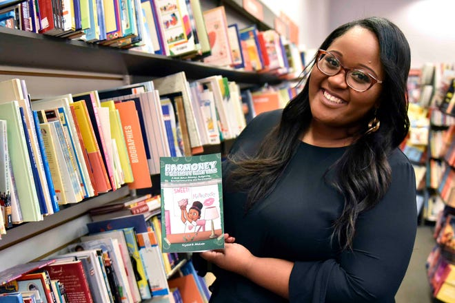 "Crystal McLean happily shows her new children's book, 'Harmoney & the Empty Piggy Bank,"" that will teach financial literacy to children. The book is scheduled for release later this month."