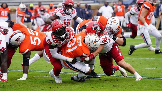 N.C. State's Drake Thomas (32) and Ibrahim Kante (28) bring down a Virginia running back in last Saturday's road win. (Photo courtesy of N.C. State Athletics)