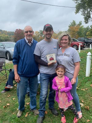 Gnadenhutten Museum Curator John Heil (left) stands with No. 1 Crock bidders Devin and Tiffany Brown and their daughter Emmalyn. Browns are the owners of Brotherhood Heating and Cooling, of Gnadenhutten.