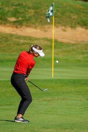 New Philadelphia's Sydney Devore chips to the hole during the Division I District Golf Tournament at EagleSticks on Monday.