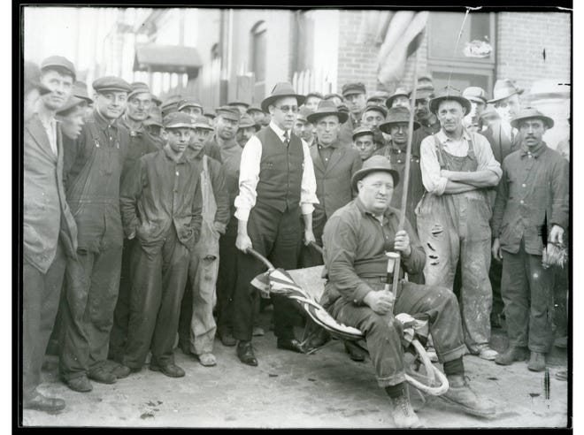 Taken about 1920, this photo shows a Buckeye Steel Castings employee sitting in a wheelbarrow holding a horn and a flag while surrounded by coworkers. In 1881, Buckeye Steel began producing steel castings and later automatic couplers for railroad cars. During the early 1900s, the company's management started programs and services in an effort to  retain workers, including the addition of washrooms, lockers, a kitchen, a cafeteria and a hospital. The company sponsored basketball, bowling, volleyball and baseball teams in addition to employee bands, orchestras and choruses. Buckeye Steel also worked with the YMCA to offer night classes and other recreational activities.