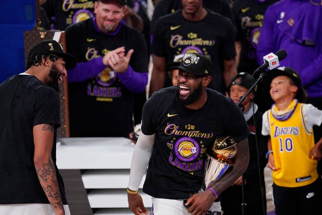 Lakers' LeBron James, center, holds the MVP trophy as he celebrates with Anthony Davis, left, and teammates after beating the Miami Heat 106-93 in Game 6 of the NBA Finals on Sunday, Oct. 11, 2020, in Lake Buena Vista, Fla.
