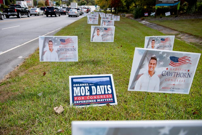 A single sign for Democratic congressional candidate Moe Davis is posted amid a grouping of signs for his opponent, Republican candidate Madison Cawthorn along U.S. Highway 64 at Dana Road in Hendersonville on Oct. 12, 2020.
