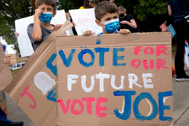 Mako Topalidis, 6, and his brother, Bobby, 8, holds signs in support of Joe Biden prior to the visit of Democratic presidential candidate Joe Biden to Cincinnati Union Terminal in Downtown Cincinnati on Monday, Oct. 12, 2020.