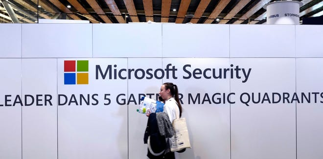 A woman walks in front of the Microsoft stand during the Cybersecurity Conference in Lille, northern France Jan. 29, 2020. Microsoft announced legal action Monday seeking to disrupt a major cybercrime digital network that uses more than 1 million zombie computers to loot bank accounts and spread ransomware, which experts consider a major threat to the U.S. presidential election.