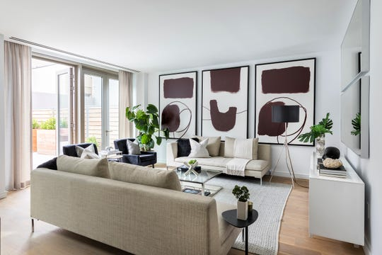 Three identical pieces of art are hung in a series in addition to two identical mirrors hung above a sideboard.