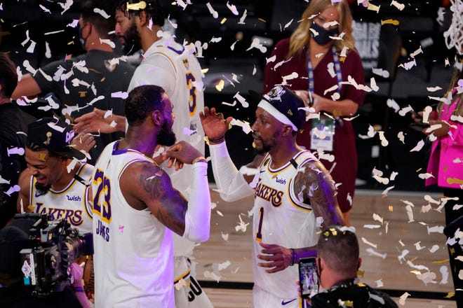 The Los Angeles Lakers' LeBron James (23) and Kentavious Caldwell-Pope (1) celebrate after the Lakers defeated the Miami Heat in Game 6.