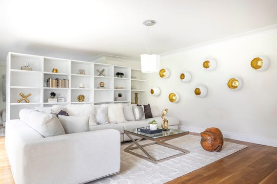 The use of interesting wall art hung in a series helps create drama and interest in this living space.