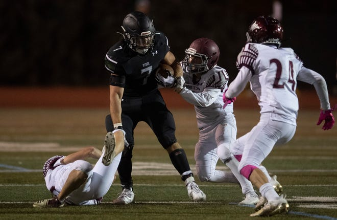 Fossil Ridge's Chris Bowerfind (7) runs between defenders in the fourth quarter of the game at French Field at Rocky Mountain High School in Fort Collins, Colo. on Friday, Oct. 9, 2020.